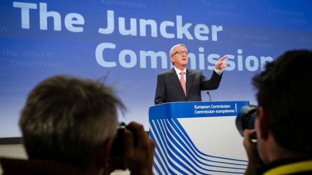 EU-Kommissionspräsident Juncker steht auf der Bühne hinter dem Rednerpult und wird fotografiert. Dahinter gross der Schriftzug: The Juncker Commission