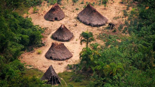Das Bild aus der Luft zeigt einige einfache Hütten auf einer Lichtung im Wald