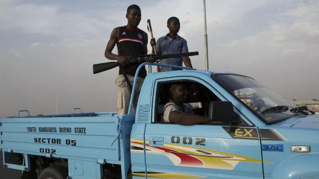 Zwei bewaffnete Angehörige einer von der Regierung unterstützten Zivilpatrouille auf einem Pickup-Truck in Maiduguri.