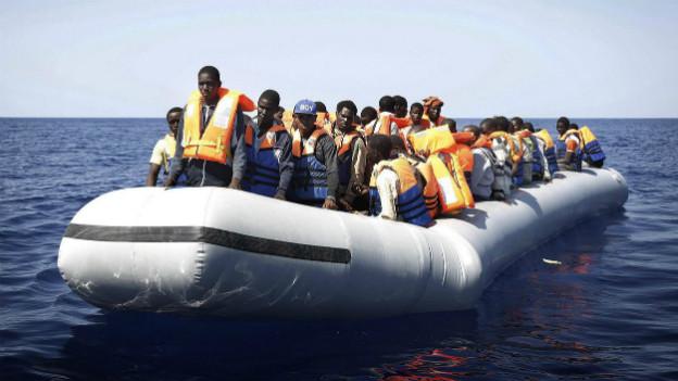 Flüchtlinge aus Afrika befinden sich auf einem Gummiboot vor der italienischen Küste.
