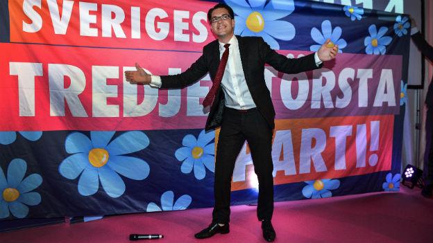 """Zu sehen ist der Parteichef der Schweden, Jimmie Akesson, vor einem bunten Poster der Partei mit dem Satz """"Drittstärkste Partei"""""""