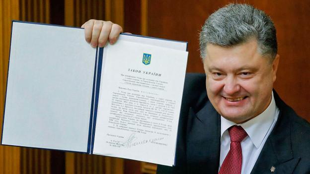 Der ukrainische Präsident Poroschenko mit dem unterzeichneten Assoziierungsabkommen zwischen der EU und der Ukraine.