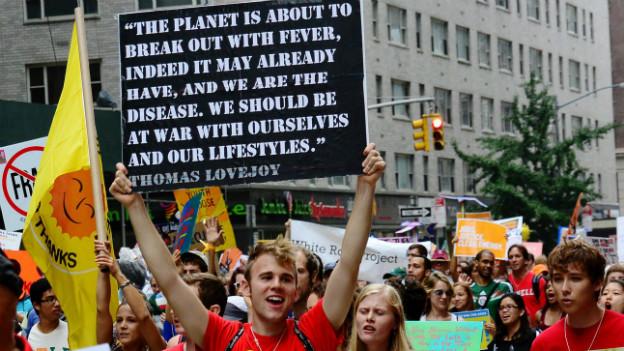Ein junger Mann hält ein Transparent in die Höhe, auf dem steht, die Erde sei «erkrankt».
