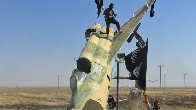 IS-Kämpfer vor einem zerstörten syrischen Flugzeug in der Stadt Raqqa im Norden des Landes (undatierte Aufnahme).