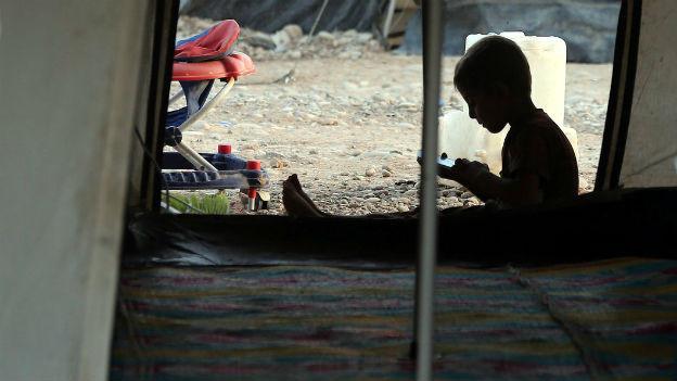 Ein Flüchtlingsjunge in notdürftigem Unterschlupf.