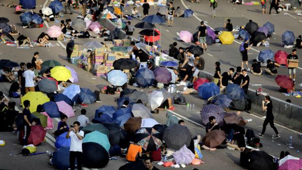 Junge Leute sitzen unter farbigen Sonnenschirmen auf der Strasse.
