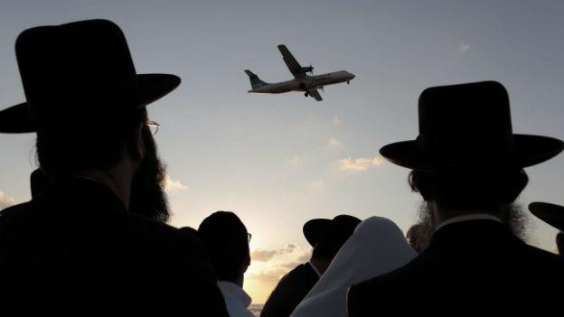 Bei Tel Aviv schauen ultra-orthodoxe Männer zu einem landenden Flugzeug hinauf.