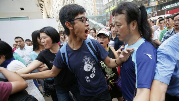 Bewegte Menschenmenge, im Vordergrund schreit ein Student einen anderen Mann an.