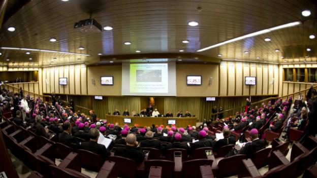 Der Papst begrüsst die an der Synode teilnehmenden Bischöfe in einem Vorlesungssaal in Rom.