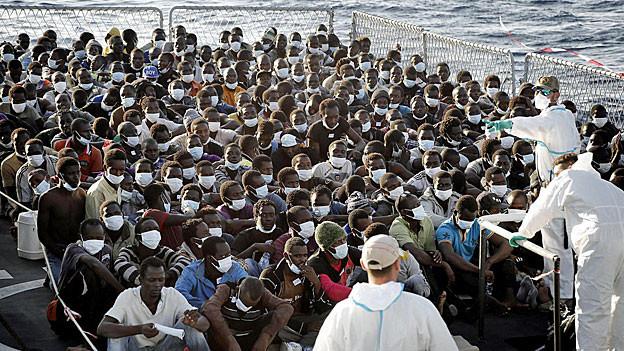 Von Bootem gerettete Flüchtlinge werden auf einem Schiff der italienischen Marine betreut.