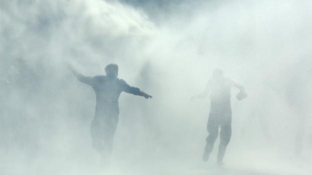 Zwei Demonstranten rennen im Strahl von Wasserwerfern.
