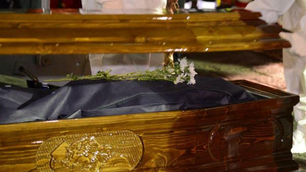 Leiche eines Flüchtlings wird am Hafen von Catania in Sarg gelegt.