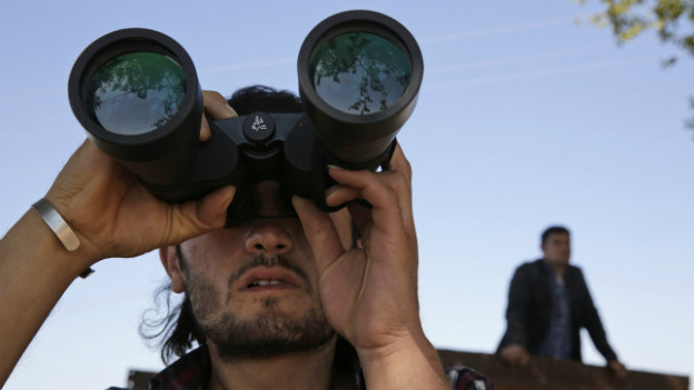 Ein junger Mann beobachtet die Gegend durch ein Fernglas.
