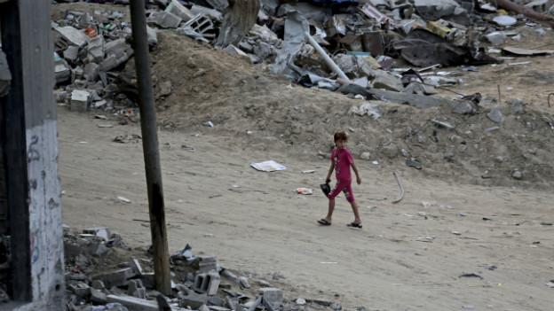 Eine Strasse, gesäumt von Trümmerteilen. Es sind Spuren des Krieges.