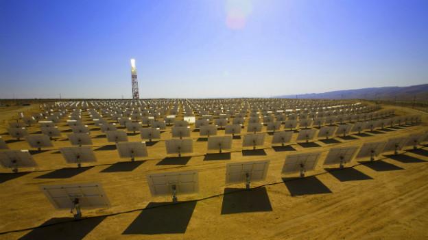 Riesige Solarpanel stehen in der Wüste der Sonne zugewandt.