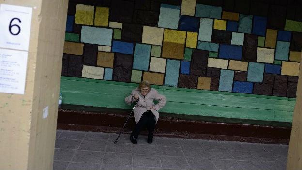 Alte Frau sitzt an einer Bushaltestelle auf einer Bank. Die Wand hinter ihr ist mit farbigen Steinen besetzt.