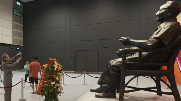 Ein Mann fotografiert eine überlebensgrosse Statue Deng Xiaopings aus Bronze.