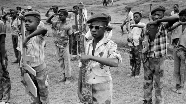 Kinder halten eine Maschinengewehr-Attrape aus Holz stramm in den Händen.