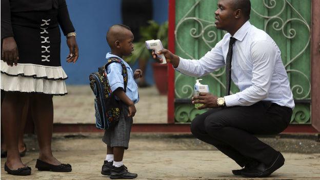 Das Bild zeigt einen Mann, der bei einem kleinen Kind Fieber misst. Mit einem Ohr-Thermometer auf einem Schulhof.