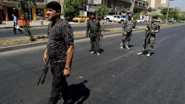 Vier irakische Soldaten in Tarnkleidung und mit Gewehren patroillieren auf einer Strasse in Bagdad.