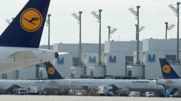 Das Bild zeigt mehrere Lufthansa-Maschinen, die auf dem Flughafen München parkiert sind.