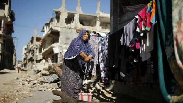 Das Bild zeigt eine Frau, die mitten in Häuserruinen bei schönestem Wetter Wäsche an eine Leine hängt.