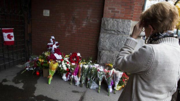 Eine Frau steht vor niedergelegten Blumen bei einer Gedenkstätte.