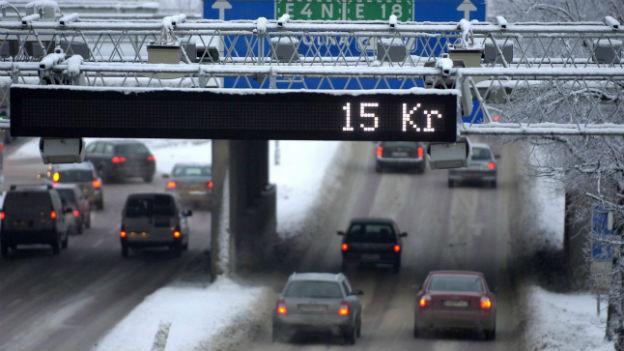 Eine Leuchtanzeige über einer Autobahn ins Zentrum von Stockholm zeigt den Preis an für die Congestion Charge: 15 Kronen.
