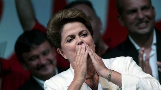 Dilma Rousseff steht auf einem Rednerpodest und wirft ihren Fans Kusshändchen zu.