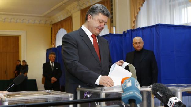 Der ukrainische Präsident Petro Poroschenko wirft seinen Wahlzettel in eine Urne. Im Vordergrund sind mehrere Mikrofone zu sehen.