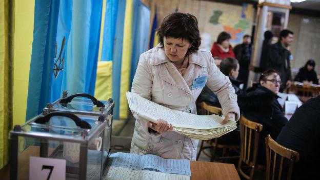 Eine Frau leert eine Wahlurne in einem Wahllokal in Kramatorsk.