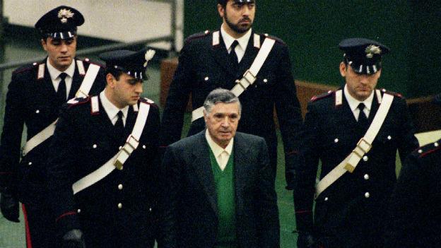 Polizisten führen Toto Riina, den Boss der Bosse, in Palermo in einen Gerichtssaal.