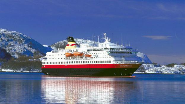 Das Bild zeigt ein Kreuzfahrtschiff der norwegischen Hurtigruten bei schönstem Wetter vor verschneiten Bergen.