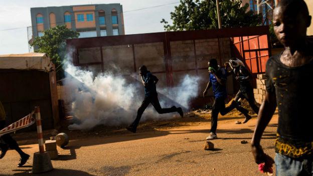 Das Bild zeigt, wie Menschen davon rennen in der Innenstadt von Ouagadougou. In der Bildmitte ein Feuer.