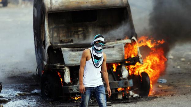 Das Bild zeigt einen Palästinenser vor einem brennenden Lastwagen.