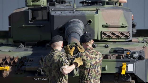 Zu sehen sind Rekruten, die an einem Panzer manipulieren.