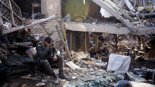Ein Polizist sitzt in den Trümmern einer Polizeistation, die bei einem Anschlag zerstört wurde.