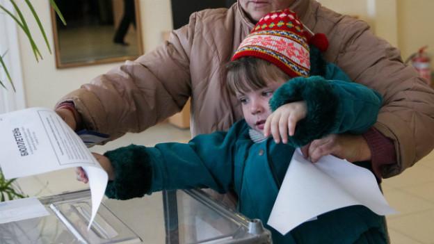 Ein kleines Mädchen wird von einer älteren Frau hoch gehalten, um einen Stimmzettel in die Urne zu legen.
