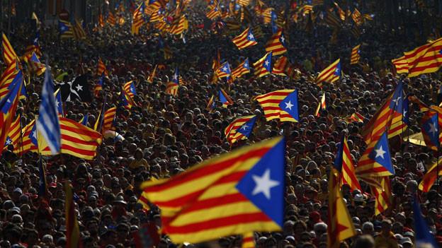 Fahnenschwenkende Demonstranten kämpfen für Kataloniens Unabhängigkeit.