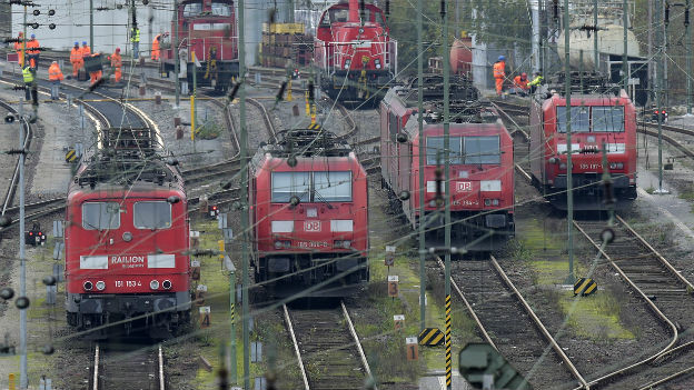 Vier Loks stehen nebeneinander auf den Geleisen, im Hintergrund stehen ein paar Rangierarbeiter in oranger Kluft.