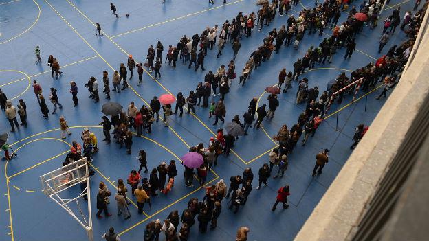 In einer Turnhalle, leicht von oben Fotografiert, stehen viele Menschen, die auf die Stimmabgabe warten.
