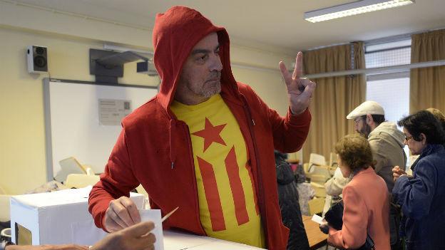 Ein Mann steht an der Abstimmungsurne, wirft seinen Zettel ein und macht das Victory-Zeichen. Er trägt ein T-Shirt mit der Katalonien-Flagge.