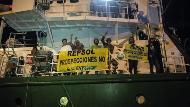 Greenpeace-Demonstranten demonstrieren auf einem Boot gegen den Repsol-Konzern.
