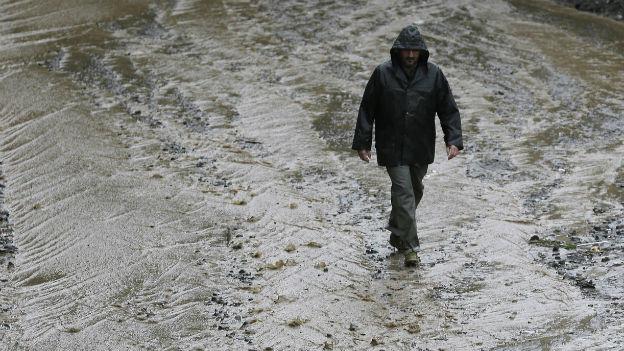 Ein Mann läuft auf einer überfluteten Strasse in Voltri bei Genua.