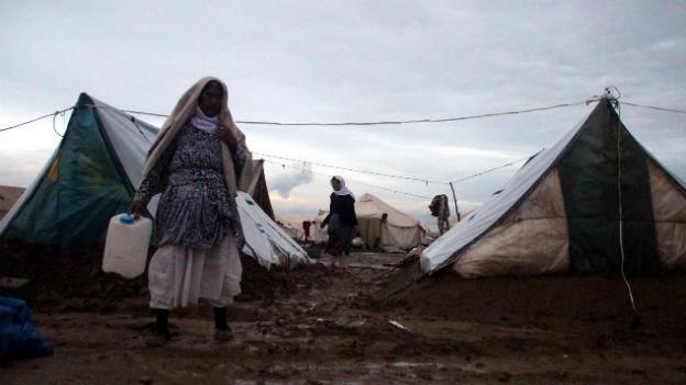 Eine Frau steht vor einem Zelt in einem Flüchtlingslager im Nordirak.