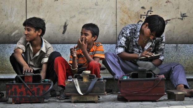Drei indische Kinder arbeiten als Schuhputzer und warten am Strassenrand auf Kundschaft.