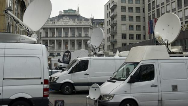 Fernsehübertragungs-Wagen warten vor dem Palais Cobourg.