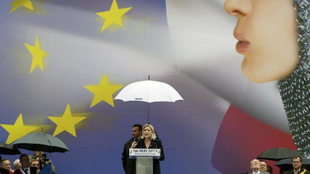 Auf einem Plakat des Front National bläst eine Frau die Sterne der EU-Flagge durcheinander.