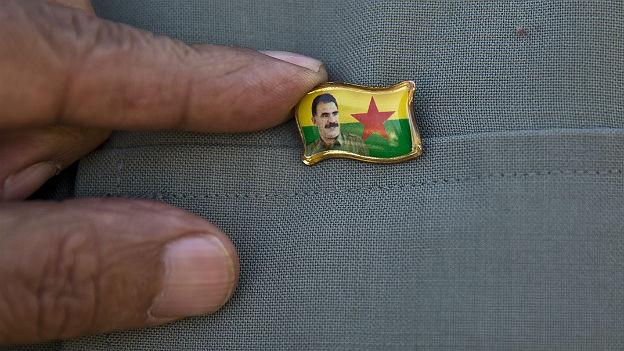 Portrait von Abdullah Öcalan auf einem Pin, an einer Jacke.