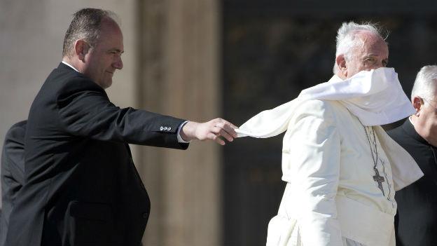 Das Bild zeigt den Papst wie er über einen Platz schreitet, der Wind verweht seine Robe, ein Wächter versucht die Robe zu richten.